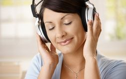 Woman listening music on headphones Stock Photos