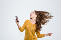 Woman listening music in headphones and dancing. Portrait of a cheerful cute woman listening music in headphones and dancing isolated on a white background Royalty Free Stock Photography
