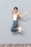 Woman listening music with headphones and jumping in the air Stock Images