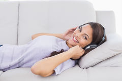 Woman listening music through headphones while lying on sofa Stock Photos