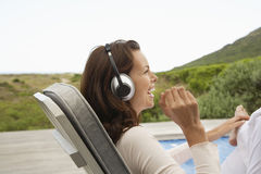 Woman Listening Music Through Headphones On Porch Royalty Free Stock Photos