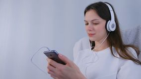 Woman is listening music in headphones on smartphone. stock video footage