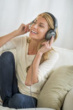 Woman Listening Music Through Headphones On Sofa Stock Photography