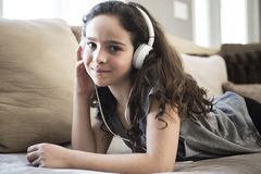 Woman listening music in headphones on sofa in room Royalty Free Stock Images