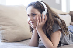 Woman listening music in headphones on sofa in room Royalty Free Stock Photo