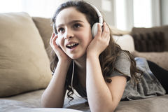 Woman listening music in headphones on sofa in room Royalty Free Stock Photography