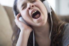 Woman listening music in headphones on sofa in room Stock Photo