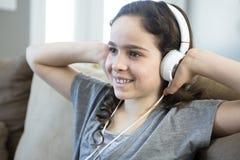 Woman listening music in headphones on sofa in room Stock Image