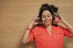 Woman listening music on headphones Royalty Free Stock Photography