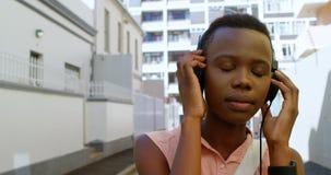 Woman listening music on headphones while walking in city street 4k