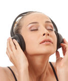 Woman listening music with headphones, on white Royalty Free Stock Images