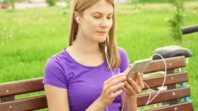 Woman listening music on mobile phone in park. Using her smartphone, relaxing after cycling. Active sportive woman with bike listening music on mobile phone in stock footage
