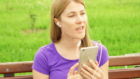 Woman listening music on mobile phone in park. Using her smartphone, relaxing after cycling. Active sportive woman with bike listening music on mobile phone and stock video footage