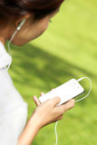 A woman listening a music in mobilephone using earphone Royalty Free Stock Images