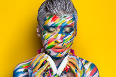 Woman listening music. Person in headphones listening songs. Painted face bright art make up bodyart faceart, lady young beautiful girl. Colorful music equalizer Royalty Free Stock Photo