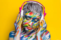 Woman listening music. Person in headphones listening songs. Painted face bright art make up bodyart faceart, lady young beautiful girl. Colorful music equalizer Royalty Free Stock Images