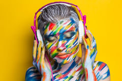 Woman listening music. Person in headphones listening songs. Painted face bright art make up bodyart faceart, lady young beautiful girl. Colorful music equalizer Stock Image