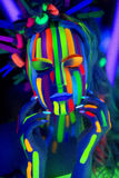 Woman listening music. Person in headphones listening songs. Painted face bright art make up bodyart faceart, lady young beautiful girl. Colorful music equalizer Stock Images