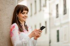 Woman listening music on phone in street Stock Photo