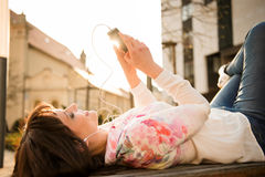 Woman listening music from phone in street Royalty Free Stock Photo