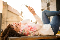 Woman listening music from phone in street Royalty Free Stock Photography