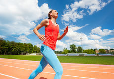 Woman listening music while running at the stadium Royalty Free Stock Photo
