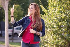 Woman listening music from smart phone with headphones outdoor a Royalty Free Stock Images