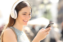 Woman listening music from a smart phone in the street Royalty Free Stock Photos