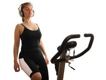 Woman listening music on spinning bicycle Stock Photos