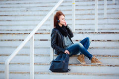 Woman listening music on stairs outdoors Stock Photos