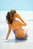 Woman listening sound of sea in shell on sea coast Royalty Free Stock Photos