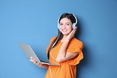 Woman listening to audiobook through headphones. On color background Royalty Free Stock Photo