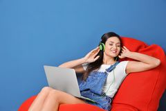 Woman listening to audiobook through headphones. On color background Royalty Free Stock Photos