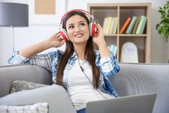 Woman listening to audiobook through headphones. At home Royalty Free Stock Image