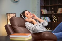 Woman listening to audiobook through headphones. At home Royalty Free Stock Images