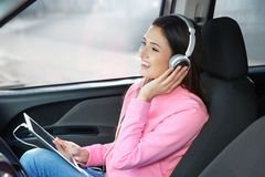 Woman listening to audiobook through headphones. In car royalty free stock images