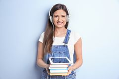 Woman listening to audiobook through headphones. On color background Stock Photo