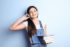 Woman listening to audiobook through headphones. On color background Stock Image