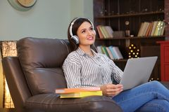 Woman listening to audiobook through headphones. At home Stock Photos