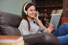 Woman listening to audiobook through headphones. At home Stock Image