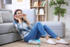 Woman listening to audiobook through headphones. At home Stock Photo