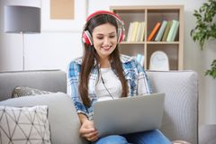 Woman listening to audiobook through headphones. At home Royalty Free Stock Photo