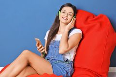 Woman listening to audiobook through headphones. Near color wall Royalty Free Stock Photography