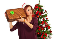 Woman listening to Christmas present Royalty Free Stock Image