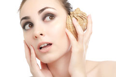 Woman listening to conch Royalty Free Stock Photo