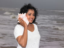 Woman listening to a conch Stock Photo