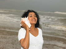 Woman listening to a conch Stock Images