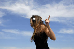 Woman listening to earphones. A view of a woman wearing a set of earphones, points to the sky as if directing a band as she listens to her favorite music.  Blue Royalty Free Stock Images