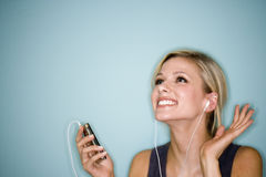 Woman listening to MP3 player. Smiling pretty woman with earbuds listening to MP3 player Royalty Free Stock Photo
