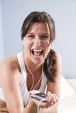 Woman listening to mp3 player, singing Stock Images